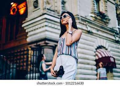 Serious female in sunglasses and trendy outfit talking on phone walking on city street. attractive young woman having mobile conversation using connection in roaming strolling during free time