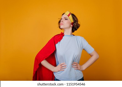 Serious female warrior in funny costume posing on yellow background. Indoor photo of curly girl in toy crown and red cloak.