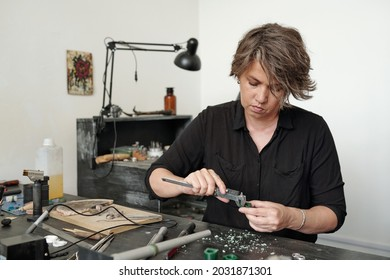 Serious femele jeweler in black shirt sitting at table and measuring blank with caliper while producing ring