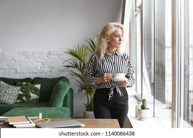 Serious fifty year old female freelancer in striped shirt and black trousers having coffee break, standing at her workplace with cup, looking through window, using portable computer for remote work