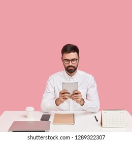 Serious financial manager prepares accounting report, holds modern touchpad, monitors news online, banking, wears glasses and formal shirt, being perfectionist, sits over pink wall with copy space