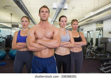 Serious fitness class posing together at the gym