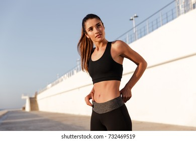 Serious fitness lady with beautiful healthy body looking camera while training near sea