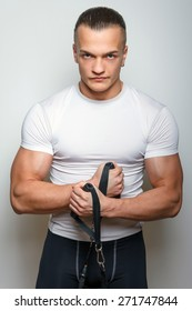 Serious fitness man in sportswear holding expander.