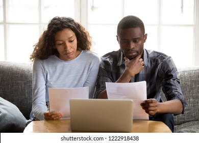 Serious focused African American couple reading paper documents, sitting together on couch at home, man and woman checking bills, bank account balance, terms of contract, mortgage, loan agreement