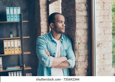 Serious focused afro american freelancer is standing near the window at home, with crossed hands, wearing casual trendy denim outfit, looks far and misses someone