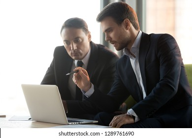 Serious focused businessmen in suits work together on online project management look at laptop discuss financial market, male partner makes business offer consult client talk give presentation advice