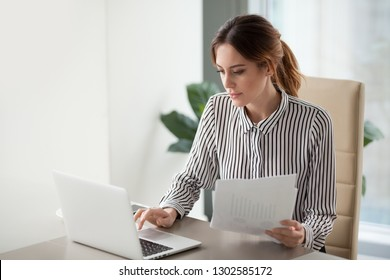 Serious focused businesswoman typing on laptop holding papers preparing report analyzing work results, female executive doing paperwork at workplace using computer online software for data analysis