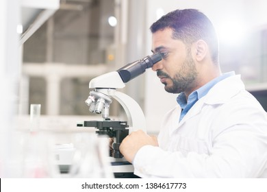 Serious focused handsome young Arabian biologist sitting at desk and using microscope while analyzing sample of modified gene