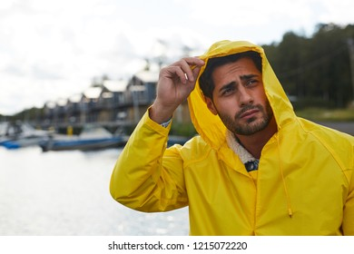 Serious frowning handsome bearded young fisherman adjusting hood of waterproof coat and looking into distance while contemplating seaport on rainy day