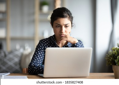 Serious frowning indian ethnicity woman sit at workplace desk looks at laptop screen read e-mail feels concerned. Bored unmotivated tired employee, problems difficulties with app understanding concept