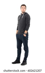 Serious frowning man in sportswear with hands in pockets looking at camera. Full body length portrait over white studio background.