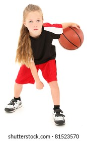 Serious girl child basketball player in uniform dribbling ball between legs over white background.