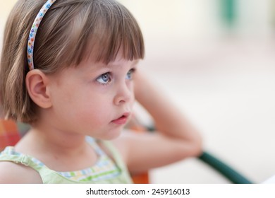 Serious girl. Cute little girl looking for someone or something at coffee table. Closeup portrait with shallow depth of field.