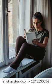 Serious girl with glasses reading book on the window