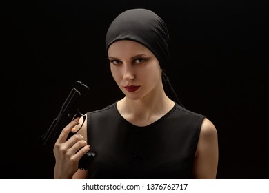 serious girl with gun looking at camera on black background