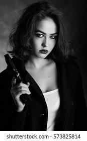 serious girl with gun on black background, monochrome