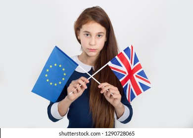 Serious girl is holding a flag of the Great Britain and Euro Union. Brexit сoncept, flags of the United Kingdom and the European Union in the arms of a sad child. Together or not?