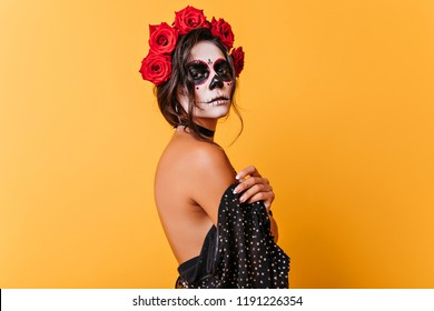 Serious girl in la muerta attire looking to camera during halloween photoshoot. Charming dead bride with roses in black hair isolated on yellow background.