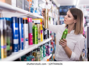Serious girl looking hair care products at cosmetics showroom