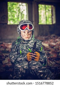 Serious girl in military uniform with knife in her hands sits near a bonfire. Disillusioned stalker in abandoned building. Girl with tired facial expression. Young stalker concept