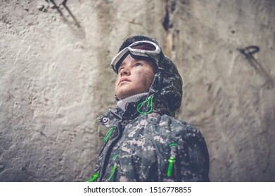 Serious girl in military uniform looking up. Disappointed and upset teenager girl. Disillusioned stalker in abandoned building. Girl with tired facial expression. Young stalker concept