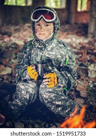 Serious girl in military uniform with mug in her hands sits near a bonfire. Disappointed and upset teenager girl. Disillusioned stalker in abandoned building. Young stalker concept