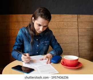 Serious girl model signs the release, there is a red mug on the table, blue glasses case and a smartphone, a woman in a denim shirt - Shutterstock ID 1957436236