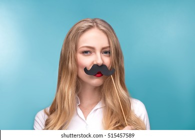 Serious girl with a paper mustache. Props for the party. Feminism concept