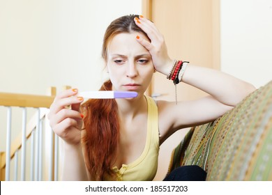 serious girl with pregnancy test at home interior
