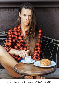 Serious girl pretty brunette model with long hair in red checkered shirt and shorts puts finger in coffee cup on vintage coach in cafe
