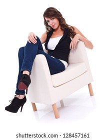 Serious girl sitting in armchair looking to camera