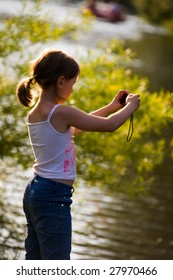 Serious girl take a photograph of river bank in summer day