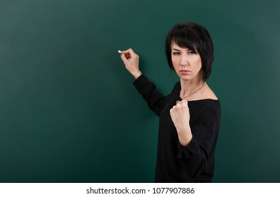 serious girl teacher posing by chalk Board, learning concept, green background, Studio shot