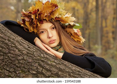 serious girl in yellow leaves crown looks at camera