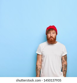 Serious good looking male model wears fashionable red hat and casual t shirt, going to have stroll, has tattooed arm, ginger beard, poses against blue wall with blank copy space on left side