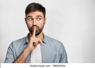 Serious good looking male with trendy hairdo, keeps fore finger on lips, tries to keep conspiracy, looks aside, says: Shh, make silence please. Isolated shot of attractive man shows silence sign