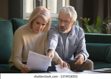 Serious grey haired mature couple calculating bills, checking finances together at home, senior retired old family reading documents, insurance paper, worried about loan, bankruptcy or money problem