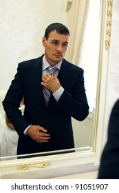 Serious groom sets straight his tie in front of mirror