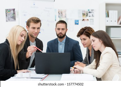 Serious group of diverse professional young business people in a meeting sitting at a table consulting information on a laptop computer
