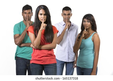Serious group of Indian friends with fingers over lips. isolated over white background.