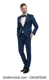 serious guy in blue tuxedo stands with hands in pockets and looks away on white background
