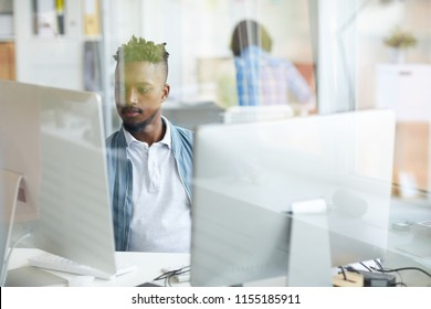 Serious guy concentrating on studying or decoding new data while sitting in front of computer monitors