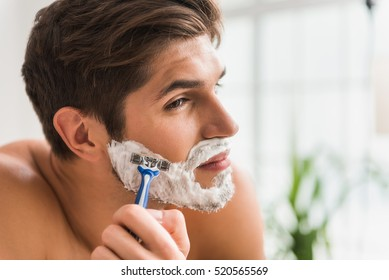 Serious guy shaving his beard