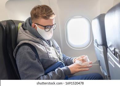 Serious guy, young man on airplane, plane in glasses and medical protective sterile mask on his face disinfect, clean hands with napkin, traveling. Coronavirus, virus concept. Pandemic covid-19.