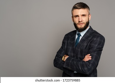 serious handsome bearded businessman in suit with crossed arms on grey background