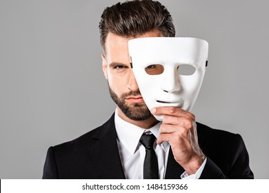 serious handsome businessman in black suit taking off white mask isolated on grey