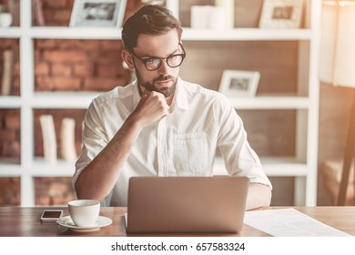 Serious handsome businessman in eyeglasses is working with laptop in cafe.