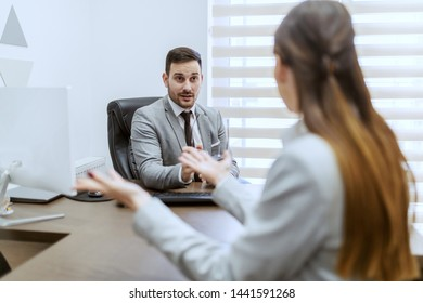 Serious handsome Caucasian CEO talking to employee while sitting in office.