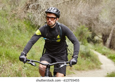 Serious handsome male biker wearing black sports clothing, helmet and eyeglasses speeding on motor-powered pedal-assist vehicle along trail in woods, having confident and self-determined look